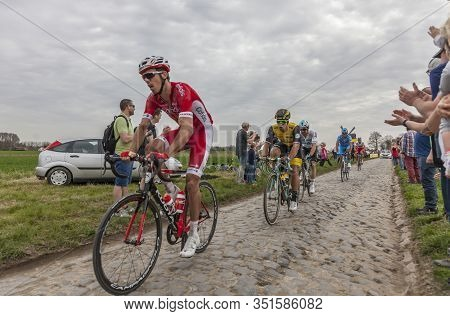Templeuve-en-pévèle, France - April 08, 2018: The Peloton Riding On The Cobblestone Road In Templeuv