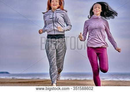 Two Women Are Jogging Along The Sandy Bank Of A Large River. Women Do Gymnastics In The Summer Morni
