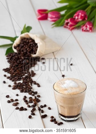 Cappuccino Or Latte With Milk Froth In A Glass. ?offee Beans In A Bag Of Coffee And Coffee Leaves On