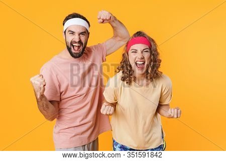 Portrait of athletic young couple wearing headbands screaming and clenching fists in triumph isolated over yellow background
