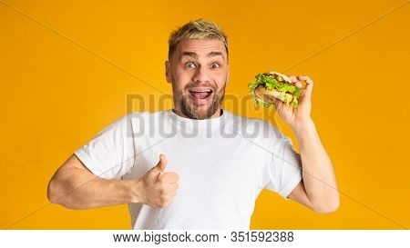 Ironic Guy Holding Vegetarian Hamburger, But Doesnt Want Healthy Food. He Shows Super Sign