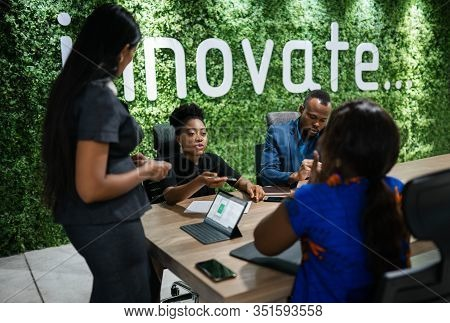 Young African Businesswoman Talking With A Group Of Work Colleagues During A Meeting Together Around