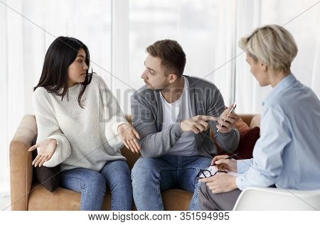 Reconciling After Infidelity. Husband Showing Phone And Blaming Cheating Wife During Couples Therapy