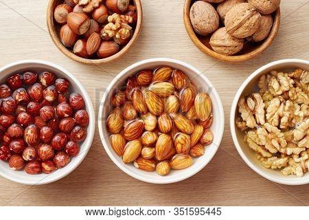 Walnuts, almonds and hazelnuts soaking in water. Soaking organic raw nuts.