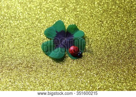 The Picture Shows Lucky Clover And A Ladybird On A Golden Glittery Background