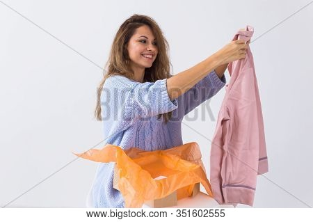 Online Shopping, Delivery And Fashion Concept - Woman Sitting On Sofa At Home Opening Online Clothin