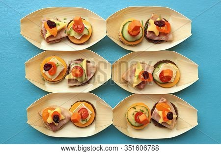 Delicious Appetizers In Small Bowls, Made From Bamboo Leaves, On A Turqoise Colored Table