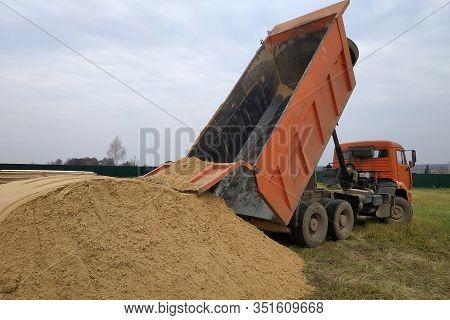 A Large Orange Dump Truck Unloads The Sand