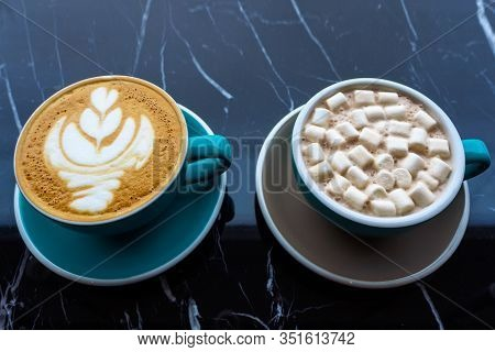 Two Cups Of Cocoa And Cappuccino On A Glossy Black Table, Top View. Coffee Break In A Cozy Cafe. Del
