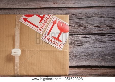 Gift box with fragile sticker  top view on wooden background