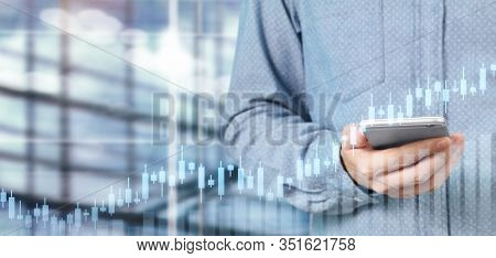 Hand Holding Smartphone Device And Touching Screen. Stock Exchange Market Concept