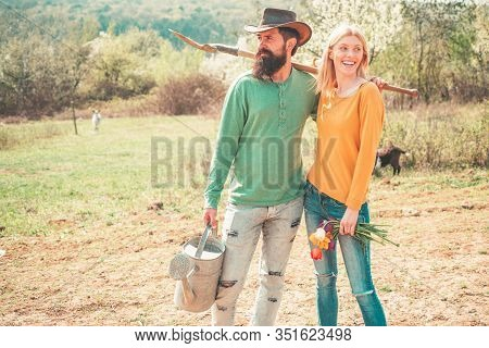 Cheerful Couple Of Farmers Standing In Vegetable Garden. Young Couple Gardening In The Garden. Portr