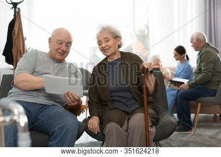 Elderly People With Tablet In Geriatric Hospice. Senior People Care