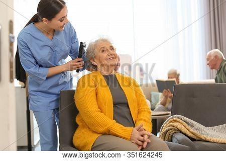 Care Worker Brushing Elderly Woman In Geriatric Hospice