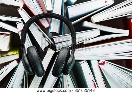 Wireless Overhead Black Headphones Lie On The Books. The Concept Of Learning Through An Audiobook. T