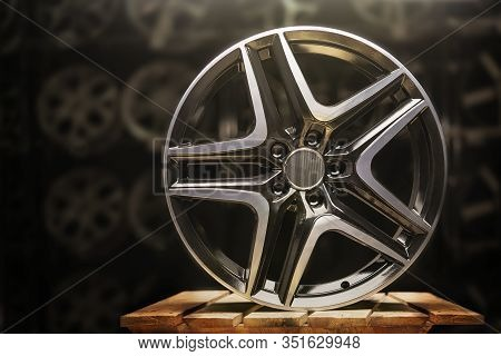 Modern Automotive Alloy Wheel Made Of Aluminum On A Black Background, Industry. On A Textured Wooden