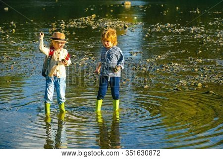 Children Throw Stones At The Stony River. Beautiful Children Throws A Rock At The River. Skipping Ro