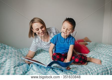 Happy Caucasian Mother And Son Family Reading Book In Bedroom. Mom And Boy Child At Home Spending Ti