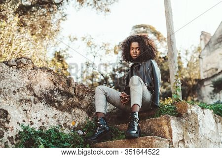 A Dazzling Young Guinean Female Is Sitting On A Concrete Step Of Old Outdoor Stairs; A Charming Afri