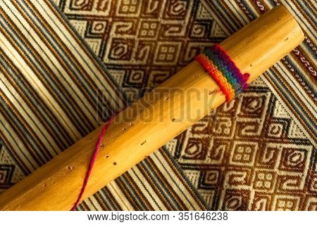 Top View Of Rainstick On Coloured Peruvian Textile. Natural Light. Andean Music Concept.