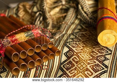 Close Up View Of Peruvian Pan Flute And Rain Stick On Traditional Colorful Textile. Natural Light. C