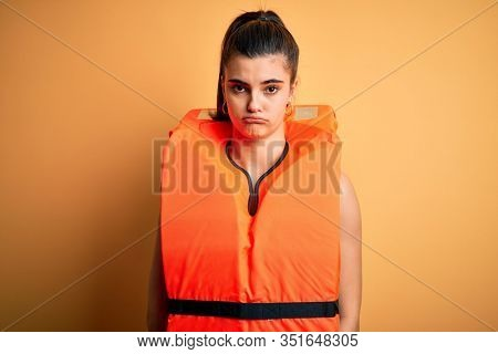 Young beautiful brunette woman wearing orange safe lifejacket over yellow background depressed and worry for distress, crying angry and afraid. Sad expression.