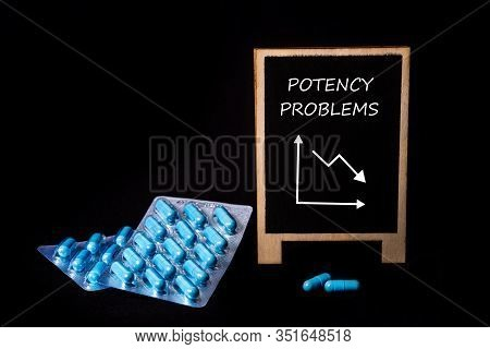 Two Packs Of Blue Capsules And Word Potency Problems On A Chalkboard. Pills For Mens Health And Sexu