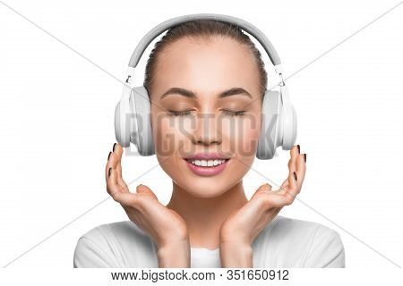 Woman With Closed Eyes In Headphones Listening To The Music. Isolated On White Background.