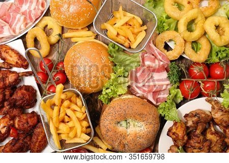 assorted of american food- hamburger, french fries, bacon, fried chicken