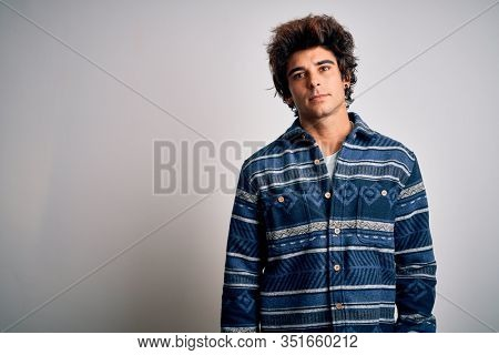 Young handsome man wearing casual shirt standing over isolated white background Relaxed with serious expression on face. Simple and natural looking at the camera.