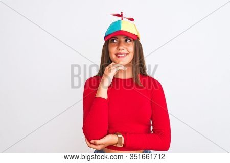 Young beautiful girl wearing fanny cap with propeller standing over isolated white background with hand on chin thinking about question, pensive expression. Smiling with thoughtful face. Doubt concept
