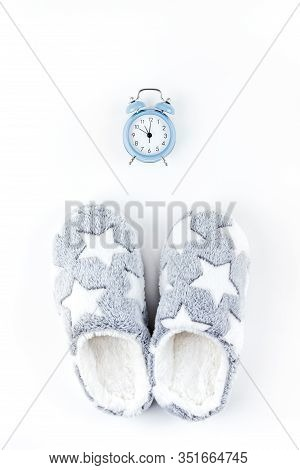 Sleep. Soft Fluffy Slippers And Blue Alarm Clock Isolated On White Background. Creative Conceptual T