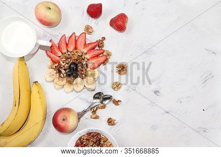 Granola And Fresh Strawberries And Grapes On A Light Table. The Concept Of Healthy And Natural Nutri