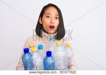 Young beautiful chinese woman recycling plastic bottles over isolated white background scared in shock with a surprise face, afraid and excited with fear expression