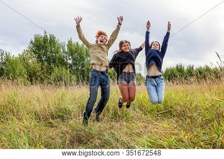 Summer Holidays Vacation Happy People Concept. Group Of Three Friends Boy And Two Girls Jumping, Dan