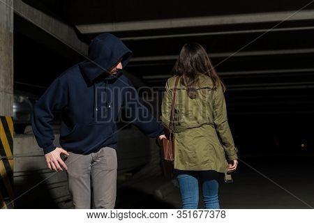 Robber Stealing From Unaware Female Victim Walking In Dark Alley