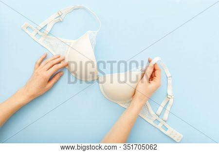 White Bra In Female Hands. Woman Choosing Holding White Bra Lingerie On Blue Background. Flat Lay Wi
