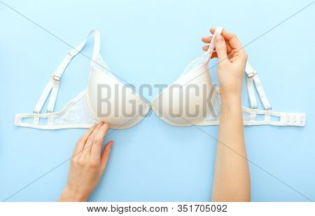 White Bra In Female Hands. White Lace Lingerie On Blue Background. Flat Lay With Lace Underwear Bra.