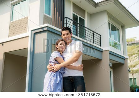 Portrait Of Asian Young Couple Standing And Hugging Together Looking Happy In Front Of Their New Hou