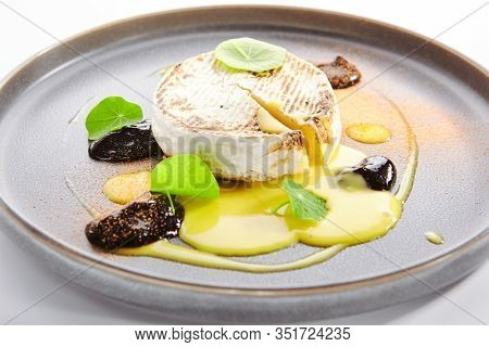 Baked Camembert in plate. Served melted cheese in white rind close up. Restaurant gourmet food, appetizer. French cuisine. Creamy soft cheese round chunk. Cow milk dairy product portion