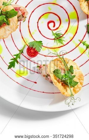Seabass tartare with fresh strawberry mint and chips. Delicious seafood decorated with berries and green leaves. Tasty fish with aromatic basil on plate. Fine dining restaurant, served dish