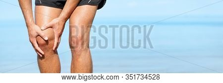 Knee pain man with painful sports injury fit runner active man athlete holding leg on outdoor summer jogging exercise panoramic banner. Fitness lifestyle.