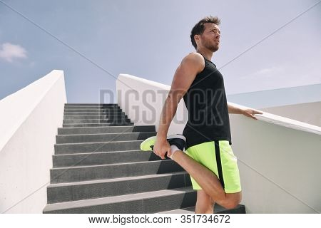 Fitness man runner getting ready to run stretching legs warm up quad stretch exercise on outdoor staircase cardio HIIT workout.