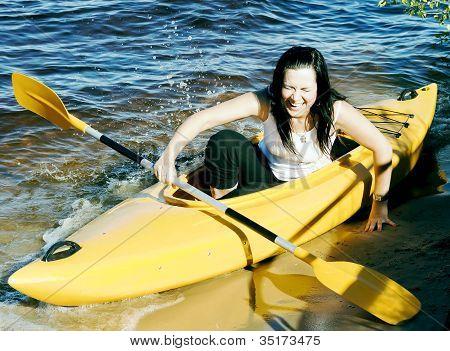 Cute girl in a yellow kayak