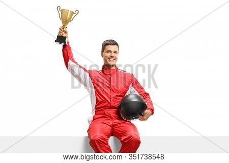 Racer in a suit holding a gold trophy cup and sitting on a panel isolated on white background