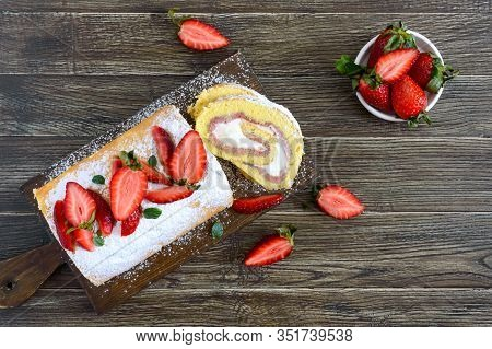Sweet Biscuit Roll With Strawberries And Cream On A Wooden Background. Top View.