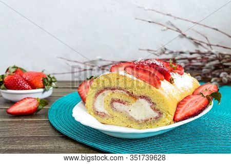 Sweet Biscuit Roll With Strawberries And Cream On A Wooden Background