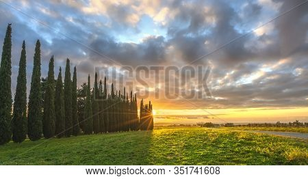 Sunset Landscape In Maremma Countryside. Country Road And Cypress Trees. Sea On The Horizon. Casale