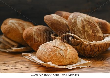 Different Buns Of Fresh Bread On A Brown Vintage Background. Freshly Baked Wheat Bread, Still Life W
