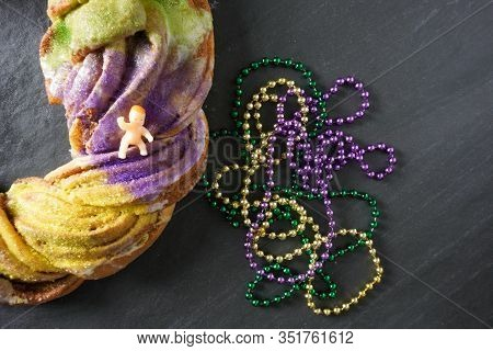 A Traditional Plastic Baby Jesus Figurine Rests On A Festive Green, Purple And Gold Mardi Gras King